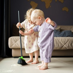 Cute little children infant boy and toddler girl in linen clothes sweeping floor in room with broom, helping mom with house chore at home. Baby boy brother and older sister spending time together