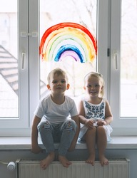 Cute little children on background of painting rainbow on window. Photo of kids leisure at home, childcare, safety joy symbol, family life. Brother and sister on vacation.