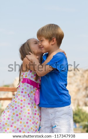 Cute little children on the playground at bright summer day