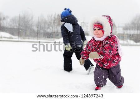 Cute little children playing on snowy field