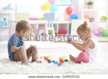 Cute little children playing while sitting on carpet at home #569859532