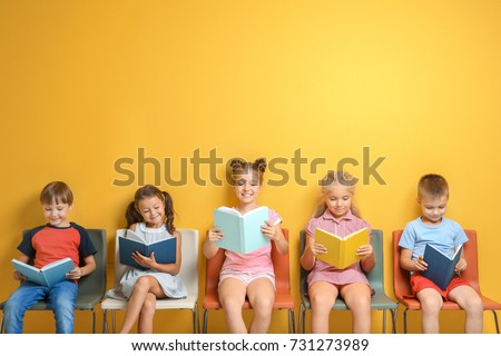 Cute little children reading books while sitting near color wall