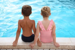 Cute little children sitting at outdoor swimming pool