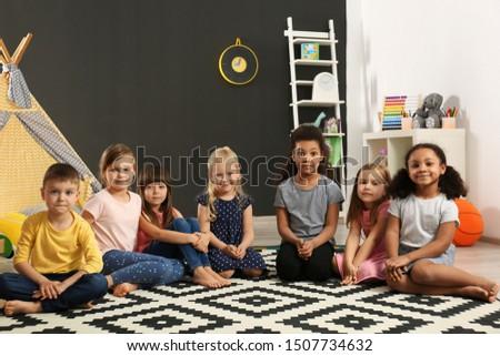 Cute little children sitting on floor indoor in kindergarten. Indoor activity #1507734632