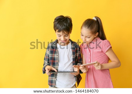 Cute little children with tablet computer and mobile phone on color background