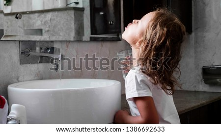 Cute little curly child girl rinses her mouth with water, looking at mirror and spits water into the sink, at domestic bathroom, side view.