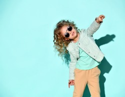 cute little curly girl with black opaque glasses on her face stands pointing one hand at you. Studio shot isolated on turquoise. Casual style, fashion for children, childhood
