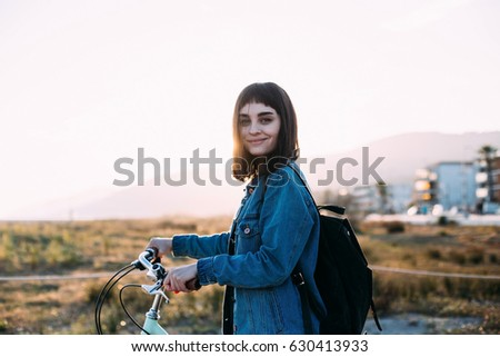 Cute little dark haired hipster girl walking her blue bicycle on the boardwalk to the beach in sunset with light lens flares of yellow and orange