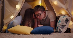 Cute little daughter and handsome young dad sharing secrets smiling while playing together in teepee. Adorable preteen girl whispering in dad ear having fun together in wigwam