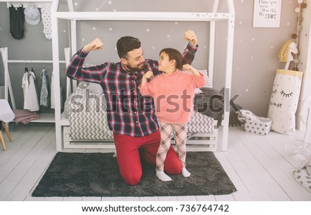 Cute little daughter and her handsome young dad are playing together in child's room. Daddy and child spend time together while sitting on the floor in bedroom #736764742