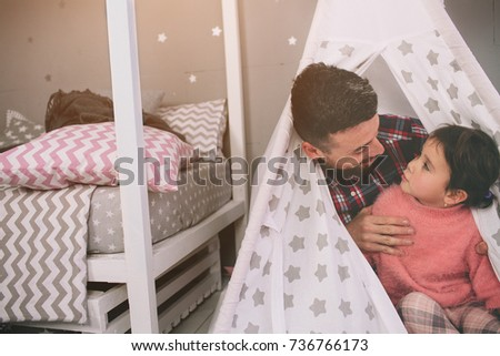 Cute little daughter and her handsome young dad are playing together in child's room. Daddy and child spend time together while sitting on the floor in bedroom #736766173