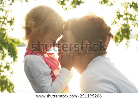 cute little daughter gently stroking her mother\'s face. mother and daughter looking at each other\'s eyes
