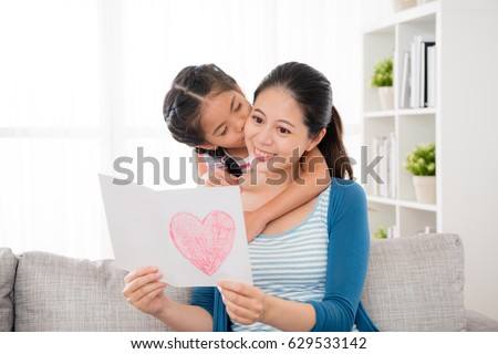 cute little daughter kiss the woman's cheek when the mother received love card gift and reading happily sitting on sofa in the living room for mother's day at home. #629533142