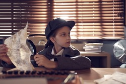 Cute little detective with document and magnifying glass at table in office