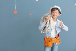 Cute little electrician showing thumb-up on color background