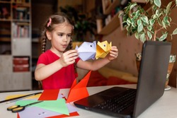 Cute little elementary schoolgirl doing origami fish with folded color paper looking video on laptop, online workshop, kids at-home activity, creativity and distant education, focus on fish