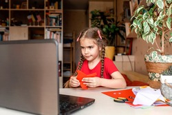 Cute little elementary schoolgirl doing origami fish with folded color paper looking video on laptop, online workshop, kids at-home activity, creativity and distant education