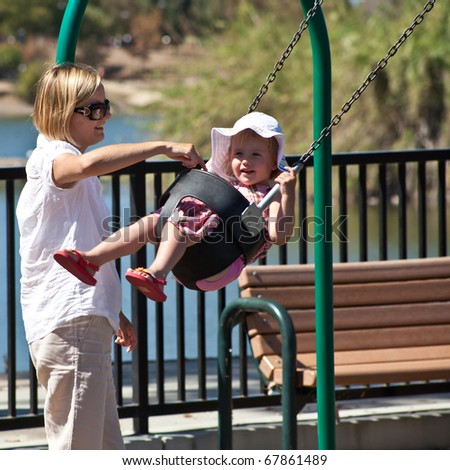 Cute little European toddler girl having fun at the playground in park