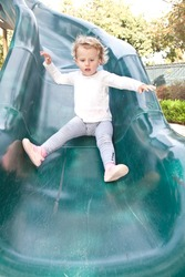 Cute little European toddler girl having fun at the playground in the park.