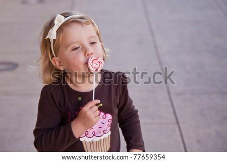 Cute little European toddler girl having fun eating heart shaped lollypop