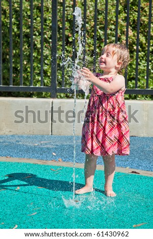 Cute little European toddler girl having fun with water at the playground in park
