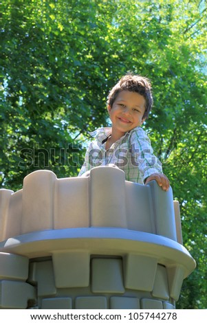 Cute little five year old boy portrait on top of a castle at the playground with green nature background