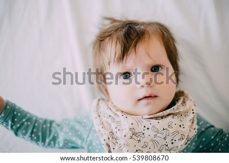 1e2454363 Cute little four month old baby girl dressed in blue bodysuit looking into  the camera #