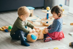 cute little girl and boy playing with toys by the home