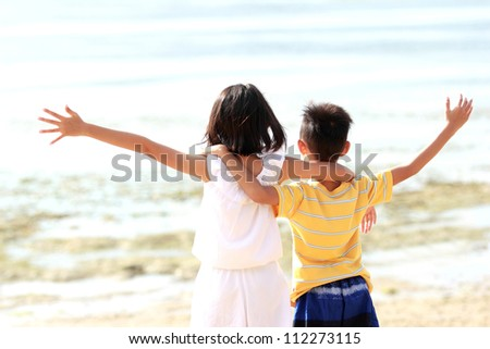 Cute little girl and boy raises their hands against blue sky