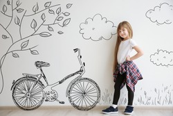 Cute little girl and drawing of bicycle on light wall background