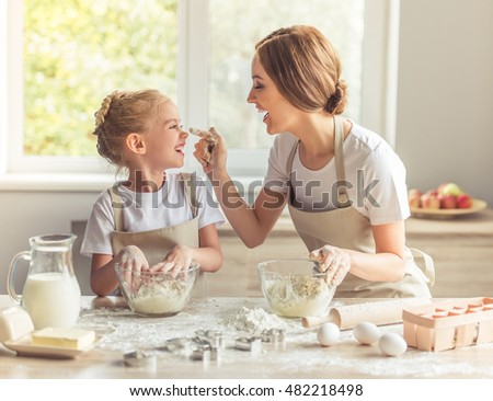 Cute little girl and her beautiful mom in aprons are playing and laughing while kneading the dough in the kitchen