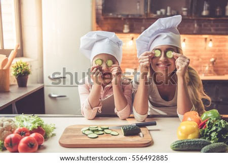 Cute little girl and her beautiful mom in chef's hats are holding slices of cucumber and smiling while cooking in kitchen at home #556492885