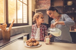 Cute little girl and her beautiful mother are smiling while drinking milk and eating muffins in kitchen. Mother is pouring milk
