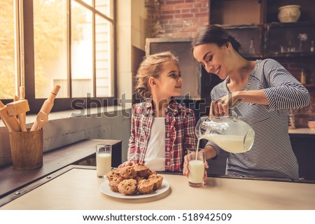 Cute little girl and her beautiful mother are smiling while drinking milk and eating muffins in kitchen. Mother is pouring milk #518942509
