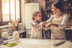 Cute little girl and her beautiful mother are sprinkling the dough with flour and smiling while baking