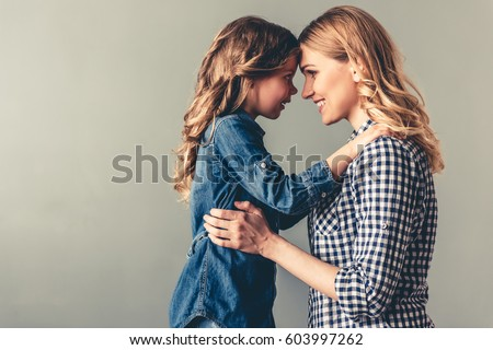 Cute little girl and her beautiful young mom are touching their foreheads, looking at each other and smiling, on gray background