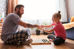 Cute little girl and her handsome bearded dad in pajamas are smiling while playing checkers in her room. Girl is sitting in front of her dad with positive emotions