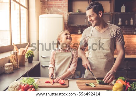 Cute little girl and her handsome dad are cutting vegetables and smiling while cooking in kitchen at home