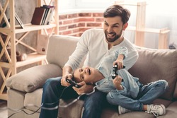 Cute little girl and her handsome father are playing game console and laughing while sitting on couch at home