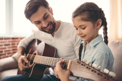 Cute little girl and her handsome father are playing guitar and smiling while sitting on couch at home