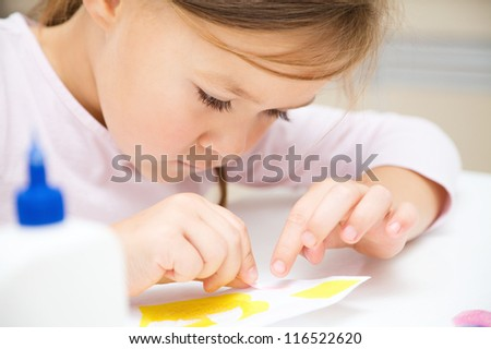Cute little girl applying a color paper using glue while doing arts and crafts in preschool - stock photo