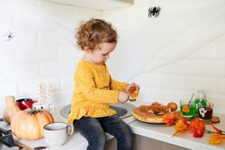 Cute little girl are sitting on the table near halloween decorations in the kitchen. she is eating pie with pumpkin