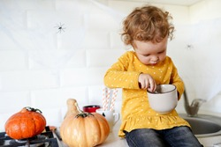 Cute little girl are sitting on the table near halloween pumpkins at home and eating tasty dessert