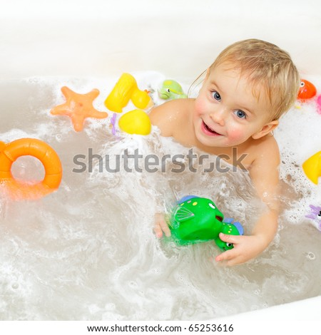 Cute little girl bathing with toys