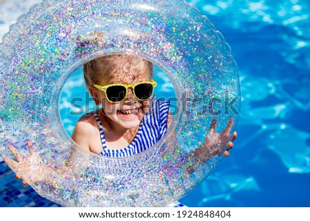 Cute little girl blonde in sunglasses laughs in the pool holding a lifeline. High quality photo Stockfoto ©