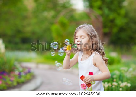 Cute little girl  blowing a soap bubbles