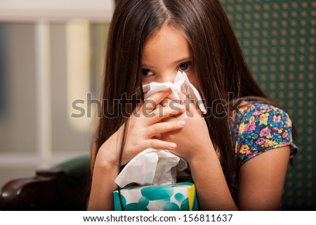 Cute little girl blowing her nose and holding a box of tissues