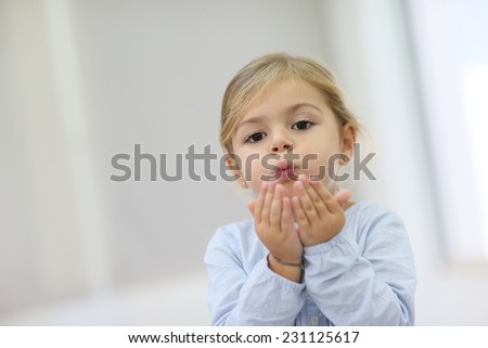 Stock Photo Cute little girl blowing kisses away