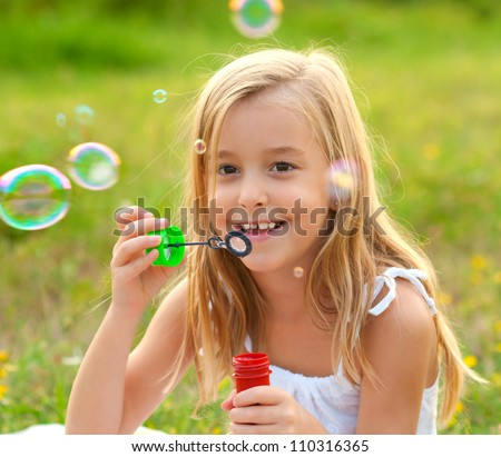 Cute little girl blowing soap bubbles on the meadow on sunny summer day.