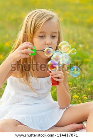 Cute little girl blowing soap bubbles while sitting on the meadow on beautiful spring day.